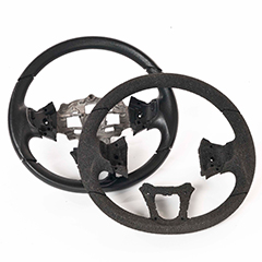 Two steering wheel shapes slightly overlapping. The background one is made from moulded ARPRO (expanded polypropylene) and has a metal insert. The foreground one is an ARPRO prototype so made from cut ARPRO