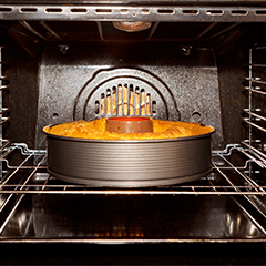 A cake in a metal tin sitting in the centre of a black oven