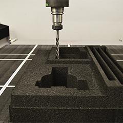 A drill cutting sections out of a black ARPRO (expanded polypropylene) square