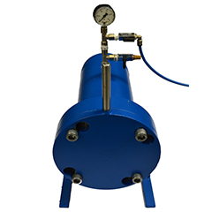 A blue pressure tank with a pressure gauge on the top with pipes coming out