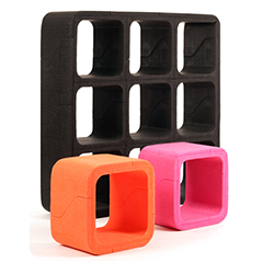 A black ARPRO (expanded polypropylene) shelving system at the back of the image, with a smaller orange and magenta cube at the front made by Movisi