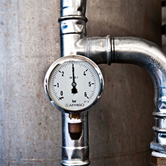 Metal pipework with a pressure gauge showing 3 bar